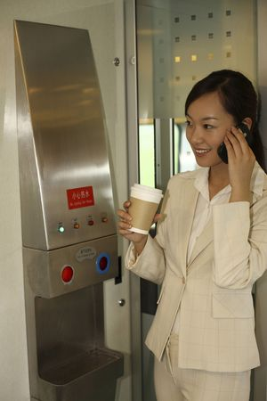 Woman holding cup of coffee while talking on the phone photo