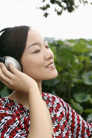 Woman listening to music on headphones with her eyes closed Stock Photo - 4631015