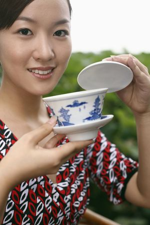 Woman enjoying a cup of chinese tea photo