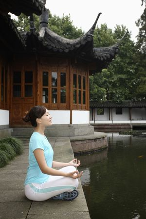 Woman meditating by the lakeside, eyes closed photo