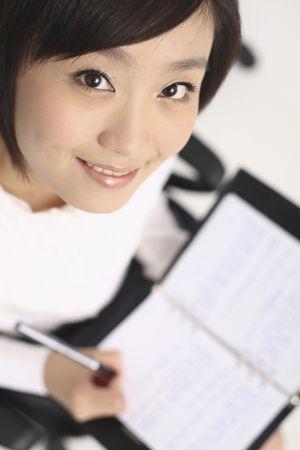 Woman writing on organizer, smiling Stock Photo - 4630730