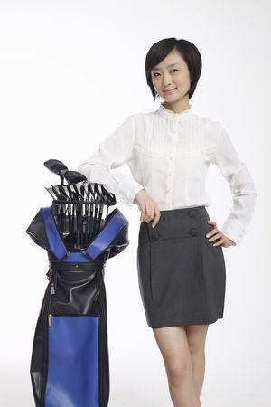 Woman posing beside golf bag photo