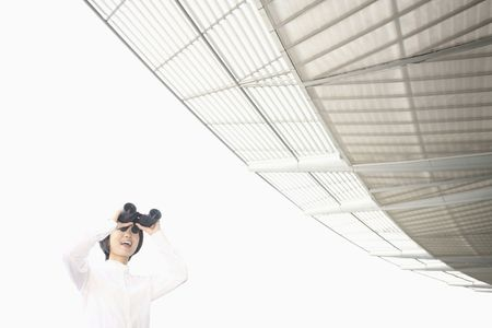 Woman using binoculars, smiling Stock Photo - 4630720