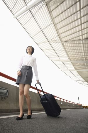 Woman walking through train station pulling suitcase Stock Photo - 4630725