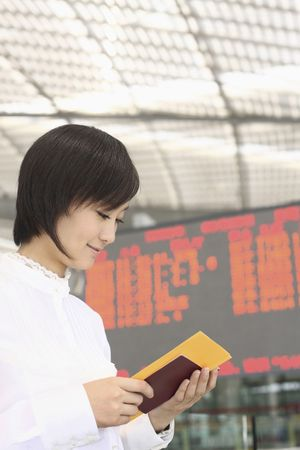 Woman looking at her passport and train ticket Stock Photo - 4630831