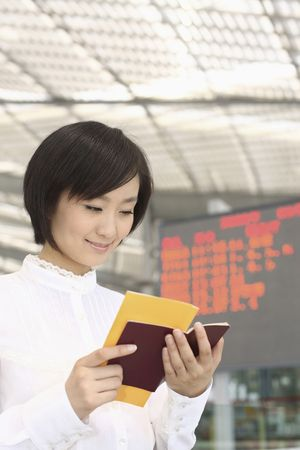 Woman checking her passport and train ticket Stock Photo - 4630787
