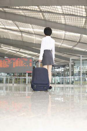 Woman walking through train station pulling suitcase Stock Photo - 4630837
