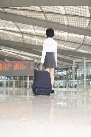 Woman walking through train station pulling suitcase Stock Photo - 4630837