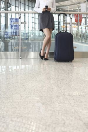 Woman text messaging on the phone, suitcase beside her Stock Photo - 4630836