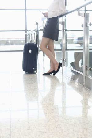 Woman text messaging on the phone, suitcase beside her Stock Photo - 4630859