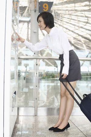 distributeur automatique: Femme � la valise en utilisant des distributeurs automatiques