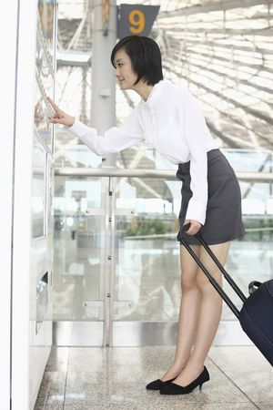 vending: Woman with suitcase using vending machine