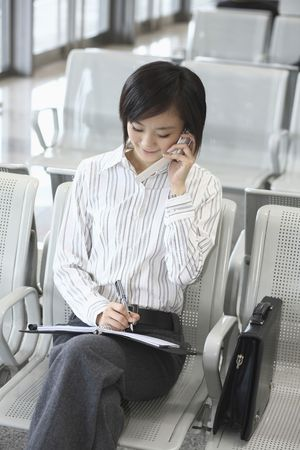 Woman writing on organizer while taking on the phone Stock Photo - 4630973
