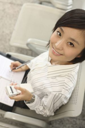 Woman writing on organizer while text messaging on the phone Stock Photo - 4630775