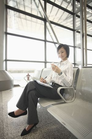 Woman writing on organizer while text messaging on the phone photo