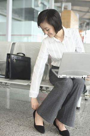Woman adjusting her shoe while using laptop Stock Photo - 4630890