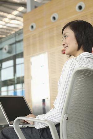 Woman using laptop while waiting at train station photo