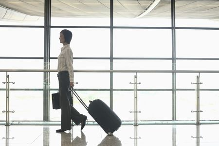 Woman walking through train station pulling suitcase Stock Photo - 4630706