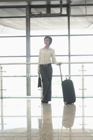Woman with suitcase and bag standing at the train station Stock Photo - 4630717