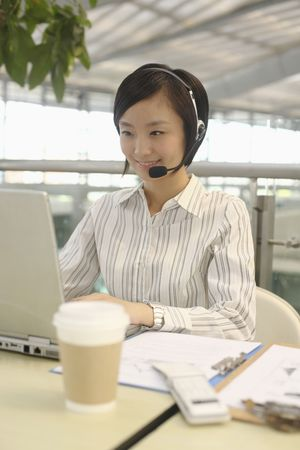 Woman talking on telephone headset while using laptop photo