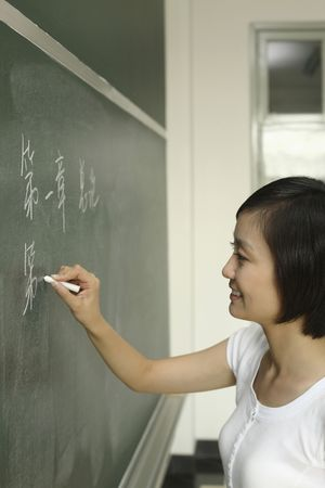 Woman writing on blackboard photo