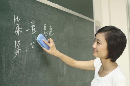 erasing: Woman erasing writing from blackboard Stock Photo