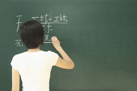 equations: Woman writing equations on blackboard Stock Photo