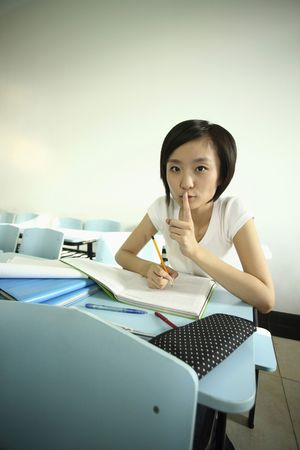 Woman with her finger on lips while writing photo