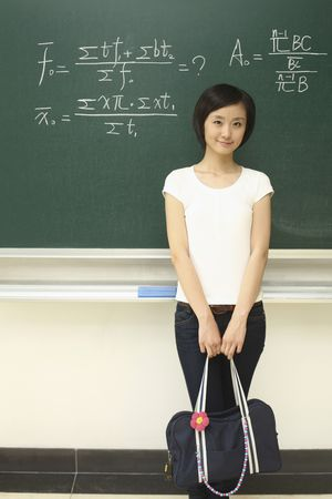 Woman with bag standing in front of blackboard
