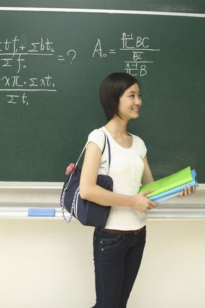 Woman with bag and books standing in front of blackboard photo