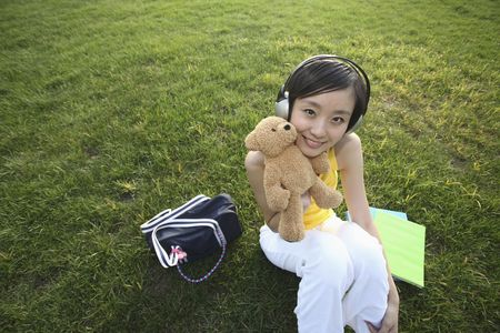 Woman with headphones holding a teddy bear photo