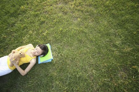 Woman with teddy bear lying on the grass listening to music photo