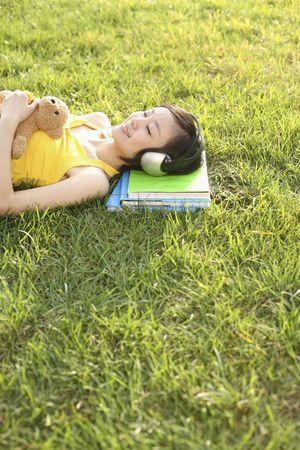 Vrouw met een teddybeer liggen op het gras te luisteren naar muziek Stockfoto