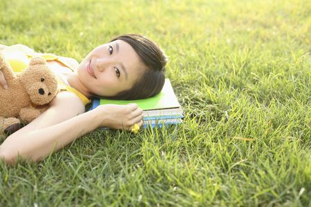 Woman with teddy bear lying on the grass Stock Photo - 4630876