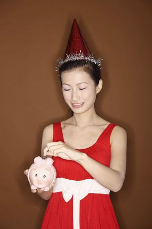 Young woman with party hat putting coin into piggy bank photo