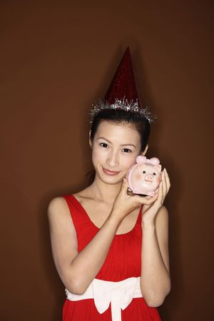 Young woman with party hat posing with piggy bank Stock Photo - 4630824