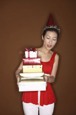 Young woman with party hat holding a stack of gift boxes photo