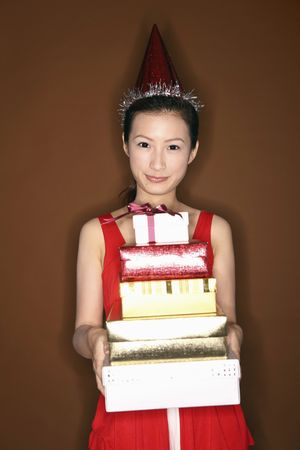 Young woman with party hat holding a stack of gift boxes, smiling photo