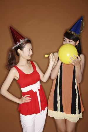 Young woman poking her friends balloon with a dart photo
