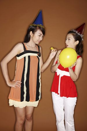 poking: Young woman poking her friends balloon with a dart