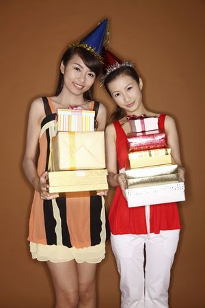 stacked up: Two young women holding stacked up gift boxes