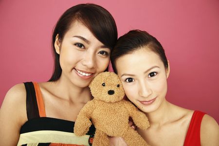 Two young women posing with teddy bear, smiling Stock Photo - 4630908