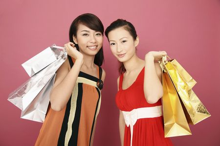 paperbags: Two young women carrying paperbags Stock Photo