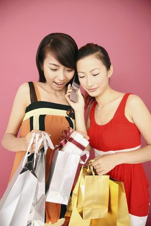 Young women with paperbags and present talking on the phone photo
