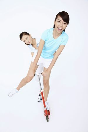 csak a nők: Two young women riding push scooter