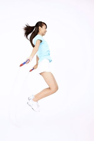 Young woman playing with skipping rope photo