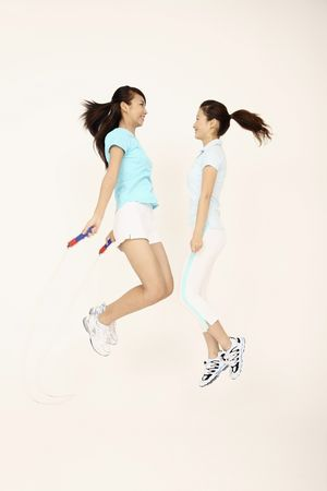 Two young women playing with skipping rope Stock Photo - 4630690