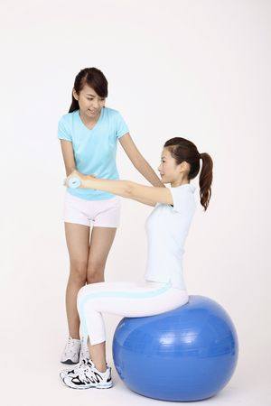 Young woman using dumbbells while sitting on fitness ball, another woman helping photo