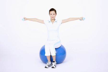 Young woman using dumbbells while sitting on fitness ball photo