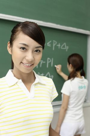 Young woman smiling, another woman writing on blackboard in the background photo